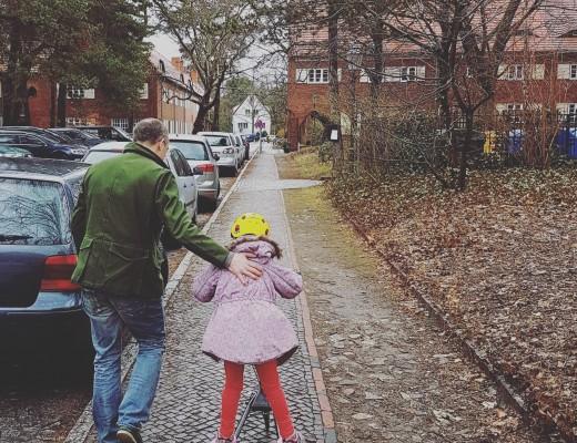 Vater hilft Tochter beim Roller