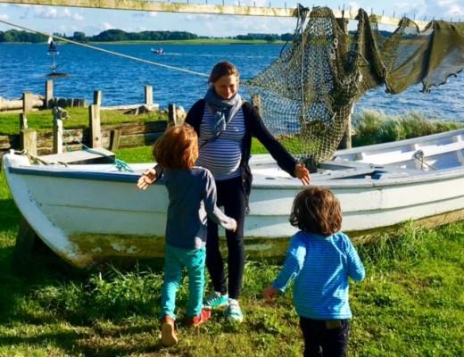 mutter mit kindern vor boot