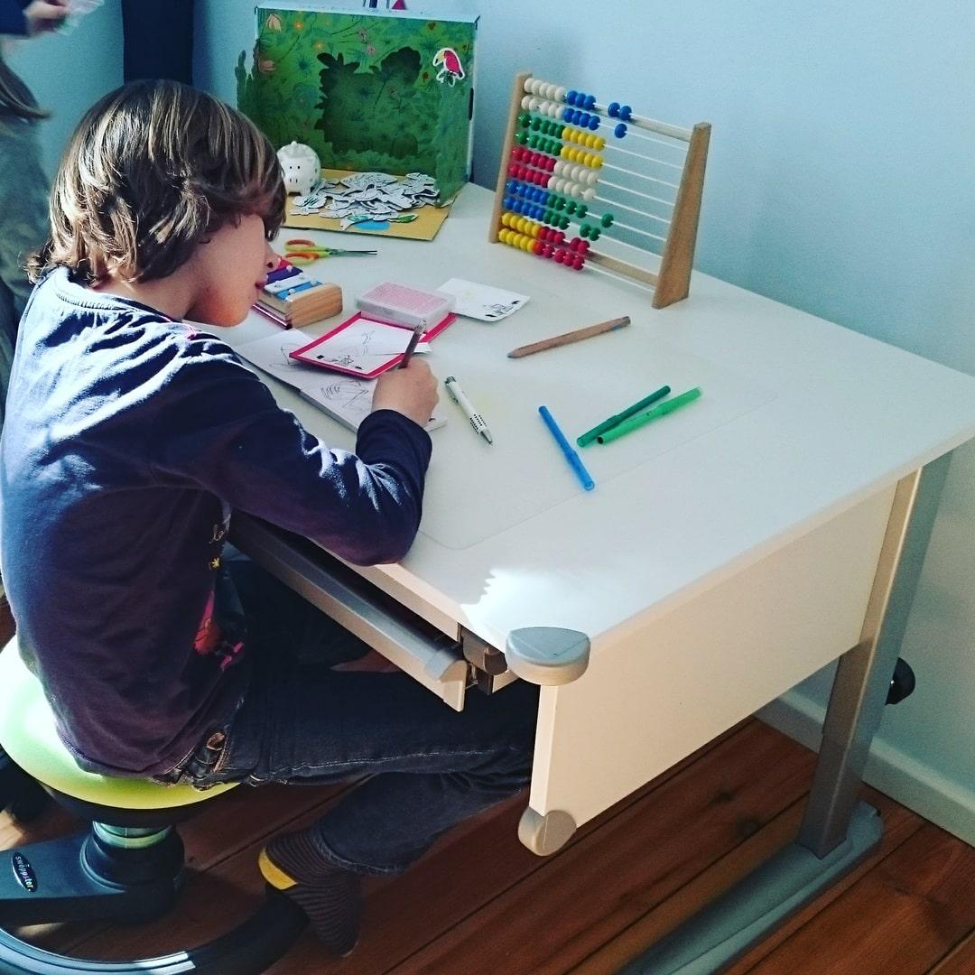 Junge macht am Schreibtisch Hausaufgaben
