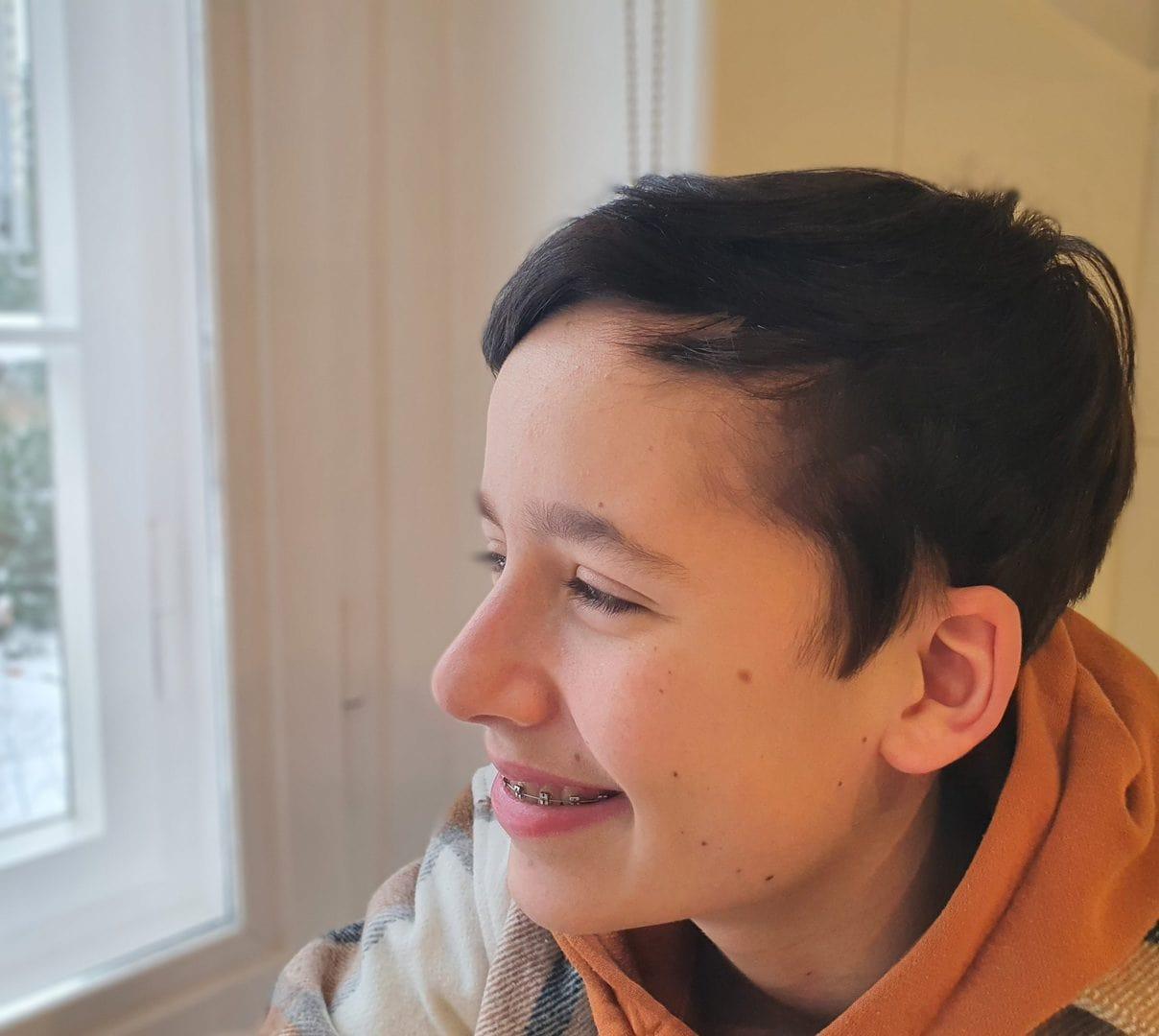 Junge mit Zahnspange schaut aus dem Fenster